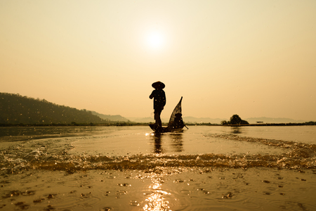fisherman on boat with sunrise background (focus at fisherman), the Mekong River in Thailand