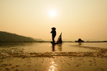 visser op boot met zons opgang achtergrond (focus op vissers), de rivier de Mekong in Thailand