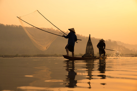 fishermans on boat with sunrise background, the Mekong River in Thailand. Stock Photo