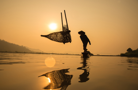Silhouette of a fisherman on boat with sunrise background, the Mekong River in Thailand. Stock Photo