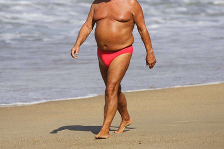 fat man walking on the beach photo