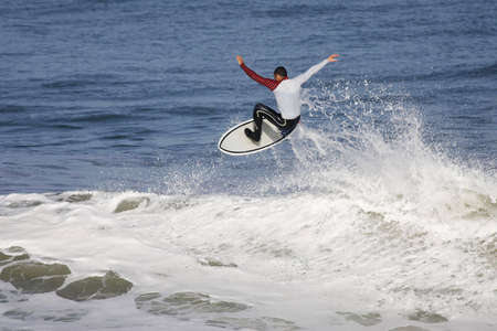 surfeur executing an aerial on the top of the wave Stock Photo - 3104057