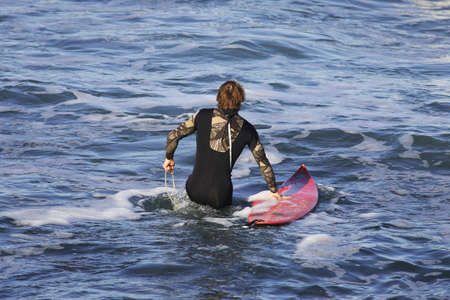 surfer in the wather with his surfboard photo