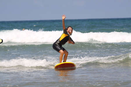 wetsuit: happy young boy surfing a little wave