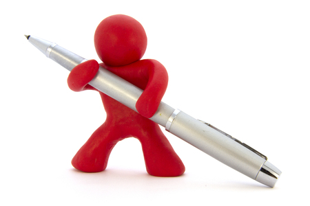Red plasticine character and silver ballpoint pen. Stationery. Isolated over white background