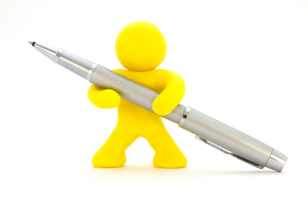Yellow plasticine character and silver ballpoint pen. Stationery. Isolated over white background