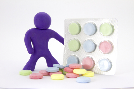 Purple plasticine character and colorful pills  tablets in the package. Pharmacy theme. Isolated on white background