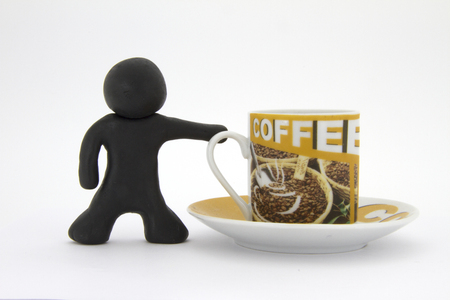 Black plasticine character and cup of coffee. Coffee set. Isolated over white background Stock Photo