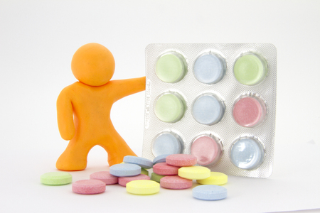 Orange plasticine character and colorful pills  tablets in the package. Pharmacy theme. Isolated on white background