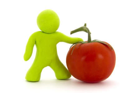 Lime green plasticine character and red tomato. Fresh fruit. Isolated on white background