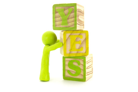 Lime plasticine character and wooden cubes. Word YES. Alphabet blocks. Isolated on white background