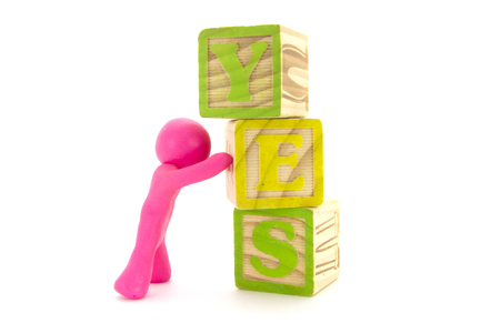 Pink plasticine character and wooden cubes. Word YES. Alphabet blocks. Isolated on white background