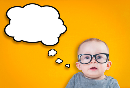Thinking baby with glasses on an orange background