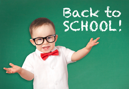 Happy smiling little boy on a chalkboard background 스톡 콘텐츠