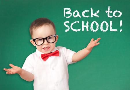 Happy smiling little boy on a chalkboard background Standard-Bild