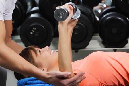 Muscle training: A girls trainer shows her the correct form of exercise with dumbbell