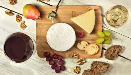 types of glasses: A photo of a tasting with two glasses of wine, red and white, different types of cheese, bread, nuts, pear, grapes, on a wooden board