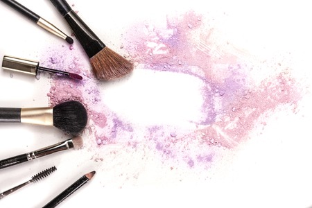 lip pencil: Makeup brushes, lip gloss and pencil on white background, with traces of powder and blush forming a frame.