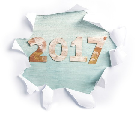 Photo of numbers forming 2017, cut out of paper with golden and white paint strokes, shot from above on light teal background, with torn paper on it. New Year greeting card or annual report design Stock Photo
