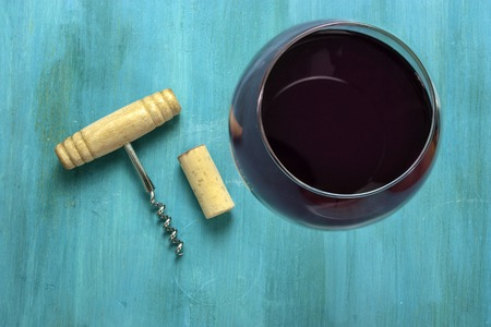 A photo of a glass of red wine with an old wooden bottle opener with a cork, shot from above on a vibrant blue wooden background texture