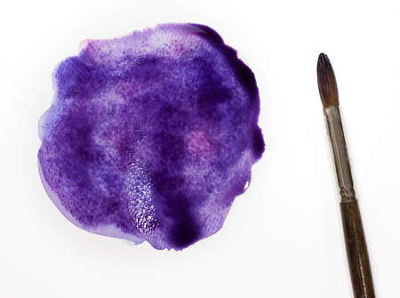 printmaking: A photo of a freshly painted purple blob with a brush, on white background. Abstract artistic texture with a place for text Stock Photo