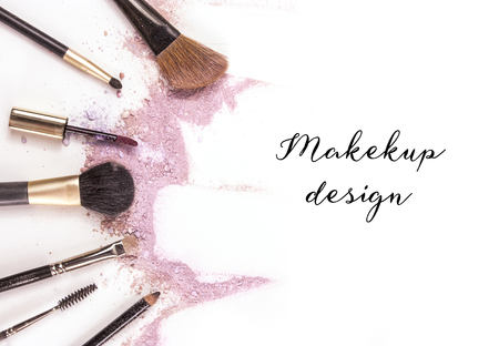 Makeup brushes, lip gloss and pencil on white background, with traces of powder and blush forming a frame.