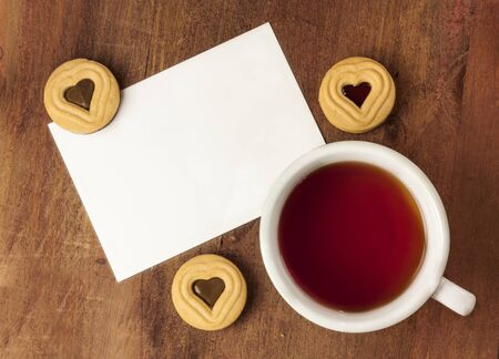 A cup of tea with cookies, with chocolate and jam filling in a heart shape in the middle, with a blank postcard for copyspace, shot from above on a dark wooden background texture