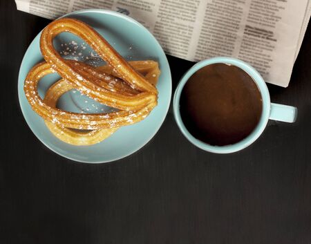 Plate of churros, traditional Spanish, especially Madrid, dessert, particularly for Sunday breakfast, with cup of hot chocolate, blurred newspaper, on dark wooden tabletop with copyspace