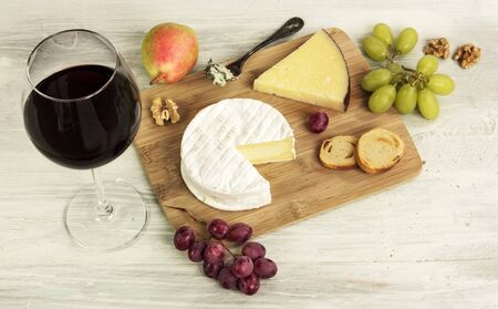 tabla de quesos: A photo of a tasting with a glass of red wine, different types of cheese, bread, nuts, pear, grapes, on a wooden board with copyspace Foto de archivo