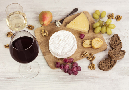 stilton: A photo of a tasting with two glasses of wine, red and white, different types of cheese, bread, nuts, pear, grapes, on a wooden board