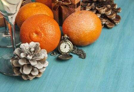 A photo of tangerines, a pine cone, and a vintage chain clock showing midnight. A New Year or Christmas greeting card on a blue background with copyspace. Selective focus