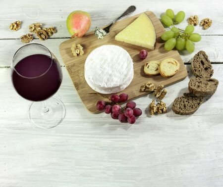 A photo of a tasting with a glass of red wine, different types of cheese, bread, nuts, pear, grapes, on a wooden board with copyspace Stock Photo