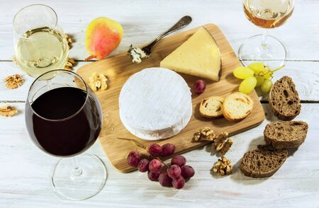 stilton: A photo of a tasting with glasses of wine, red and white, different types of cheese, bread, nuts, pear, grapes, on a wooden board with copyspace Stock Photo