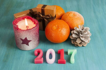 A New Year card with gift boxes, tangerines, a pine cone, and a burning candle, with the 2017 numbers, on a dark blue background