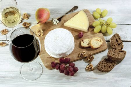 stilton: A photo of a tasting with glasses of wine, red and white, different types of cheese, bread, nuts, pear, grapes, on a wooden board