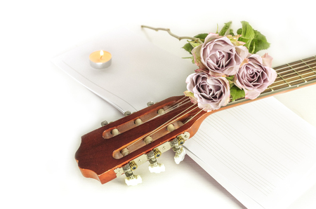 Guitar neck with roses and sheet music, on white