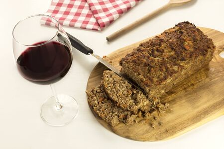warm cloth: Freshly cooked and cut meatloaf with glass of wine