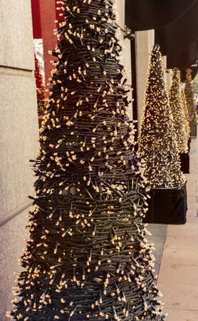 artificial lights: Row of artificial Christmas trees with fairy lights