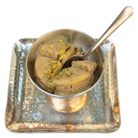 condensed: A photo of kulfi, traditional Indian ice cream, in a typical bowl, on white background. Selective focus on the dessert