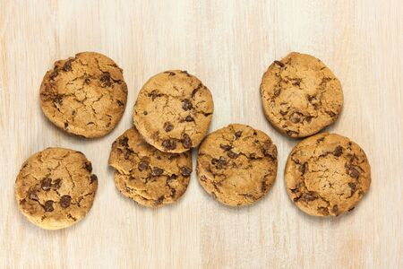 A pile of chocolate chips cookies on a wooden board texture with copy space, shot from above Stock Photo
