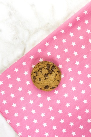 Chocolate chips cookie on a pink textile napkin