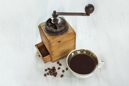 Vintage coffee grinder with beans, cup, and copyspace Stock Photo