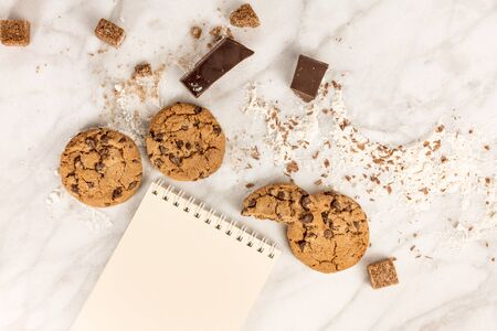 The process of making chocolate chips cookies. Overhead shot of biscuits with chocolate pieces, flour, and cane sugar around them, with a blank notepad for copy space Stock Photo
