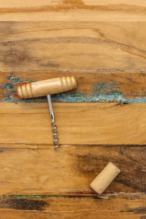 Old-fashioned corkscrew with cork, shot from above on distressed wooden background texture with plenty of copy space. Design template for wine list or a tasting invitation, slightly toned