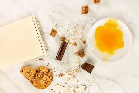 comfort food: The process of making chocolate chips cookies. Overhead shot of biscuits with chocolate pieces, flour, cane sugar, and egg yolk, with a blank notepad for copy space