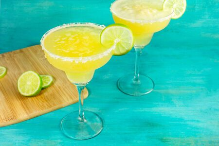 Lemon Margarita cocktails with wedges of lime on a vibrant teal background with copy space. Selective focus