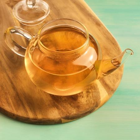 sencha: Teapot full of tea on teal texture with copyspace