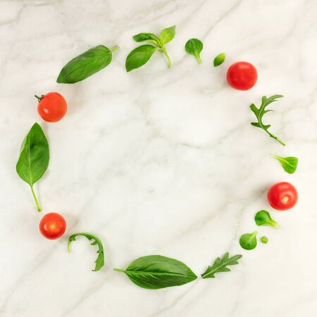 Frame of green leaves and cherry tomatoes with copyspace