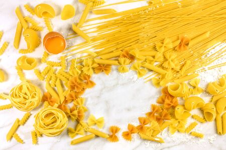 Various types of pasta with egg on marble with copyspace Stock Photo
