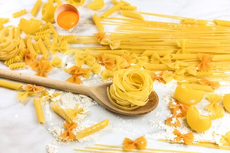 sorts: Various types of pasta on marble with flour